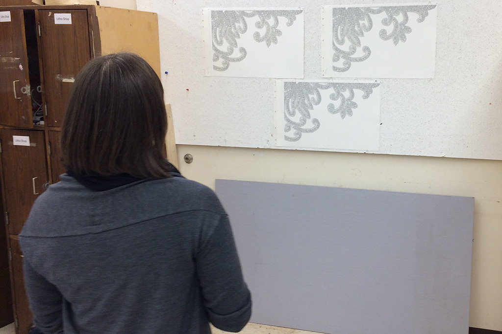 artist reviewing a variety of proofs