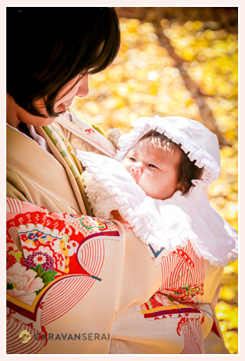 お宮参り 赤ちゃんを抱くママ ママもお着物 銀杏の葉で黄色の地面