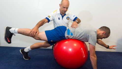 A TeamBath physiotherapist treating a man, who is lying facedown on an exercise ball