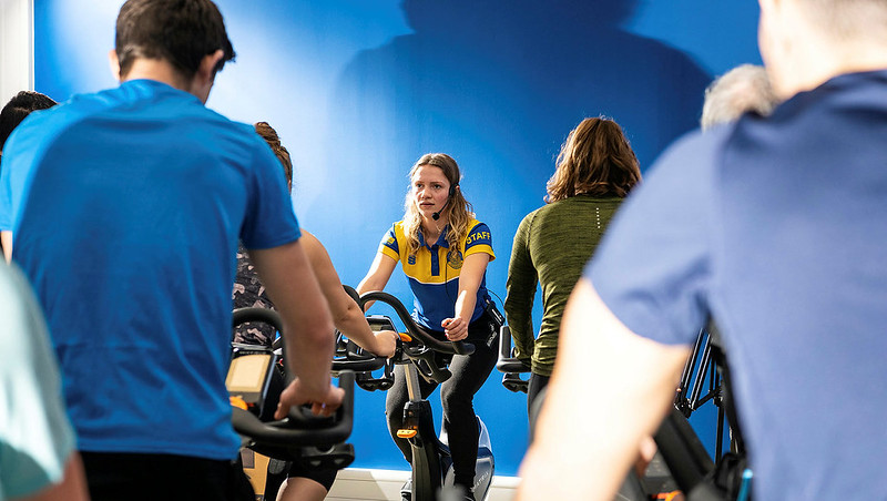 A fitness instructor leads a group on exercise bikes
