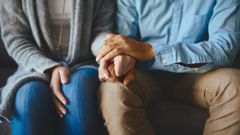 Man and woman holding hands for comfort