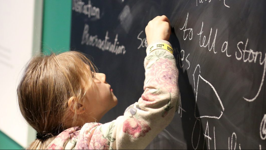 A young girl writing on a blackboard