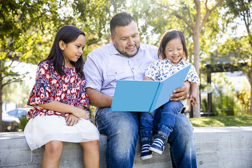 A father reads a book to his two children.