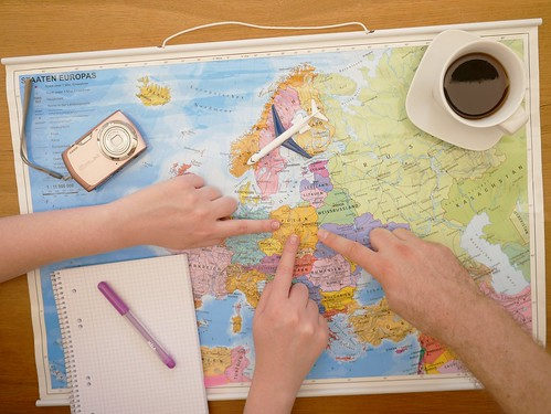 many hands surrounding a map, for travel planning. From How to Save Money and Time: Expert Shares Top Travel Planning Tips