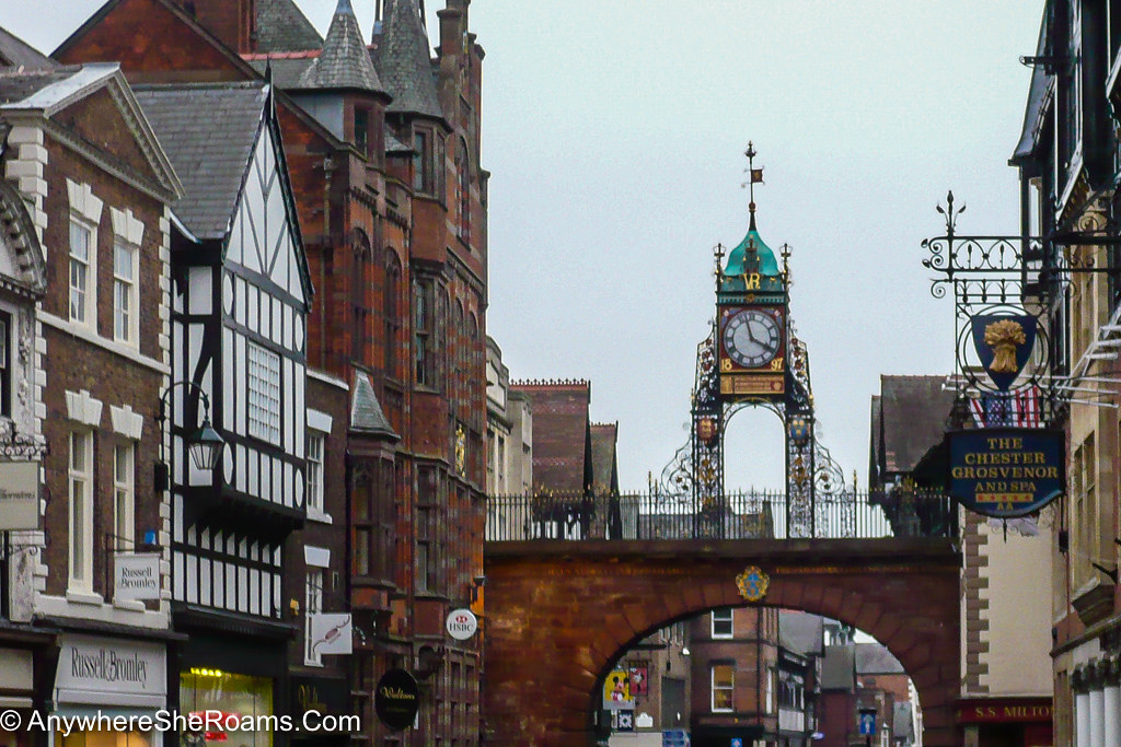 A street with traditional old English houses on it, with both wooden balck and white architecture, but also red brick one. In the middle of the street there is a bridge on top of which lies the Chester Clock, which is made out of metal, has a green rooftop, and golden details around it.