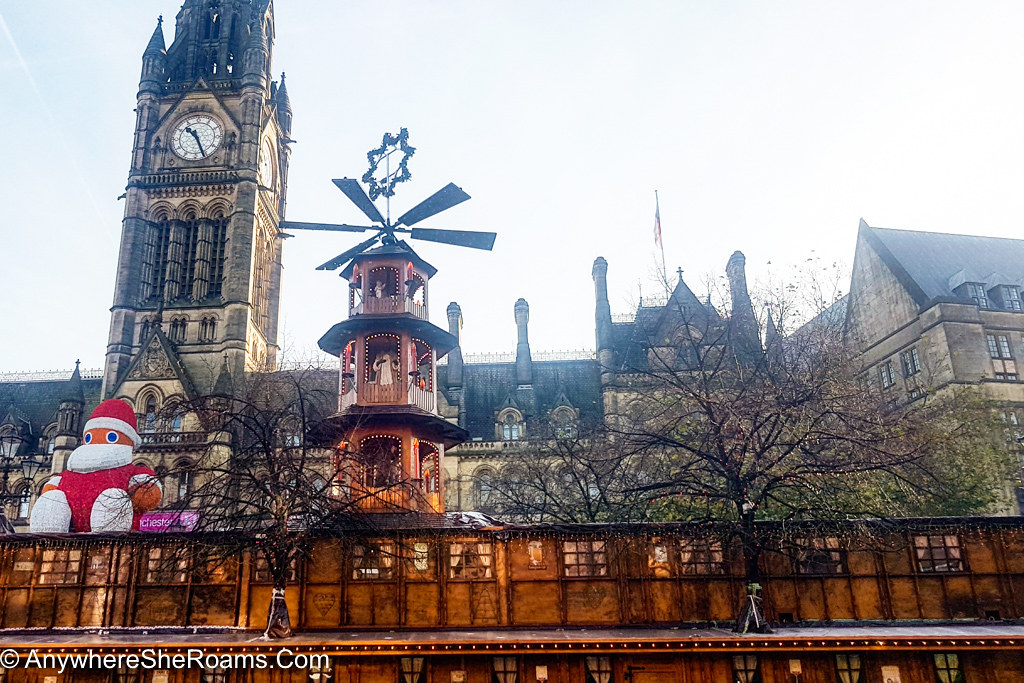 A photo taken at the Manchester Christmas Market. In the background there is a clock tower. In front one can see the decorations from the market, with a penguin dressed in a red Santa suit sitting on a rooftop of one of the cabins in the market.
