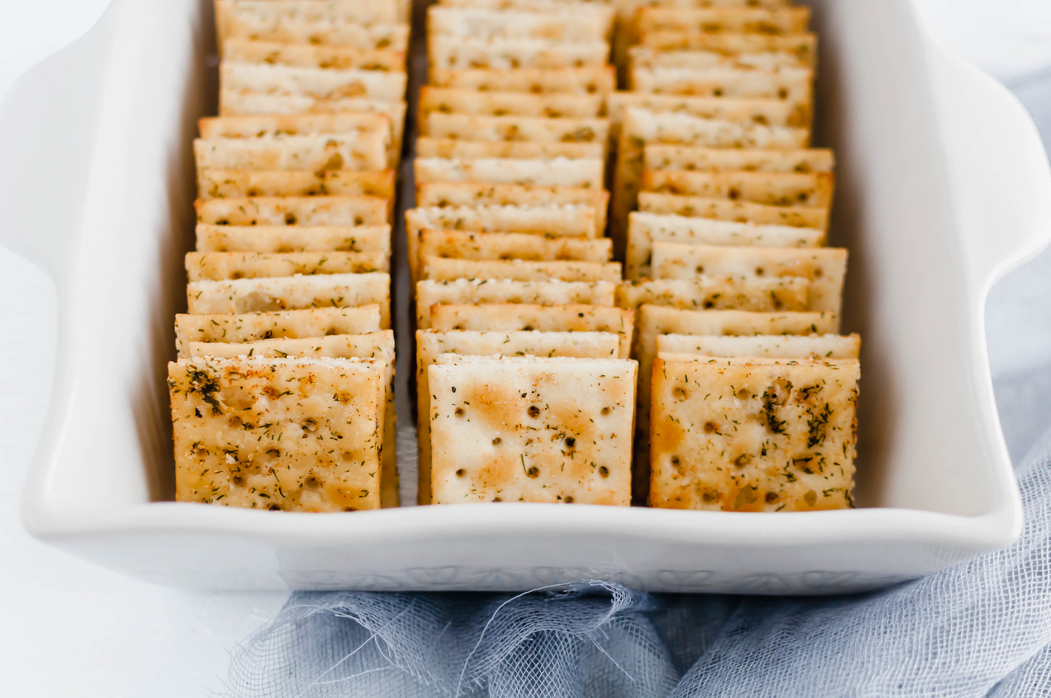 Seasoned Saltine Crackers are wonderful as a snack or a dipper for all the soups this winter. Tossed in oil, spices and herbs then baked to crispy perfection.