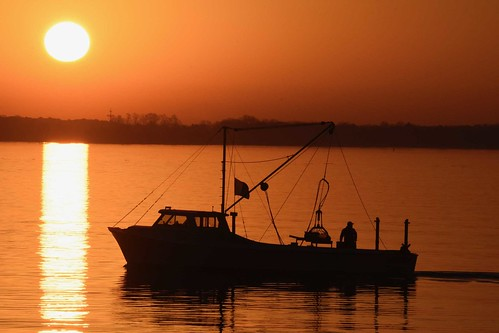 Photo of oyster boat on the water at sunrise