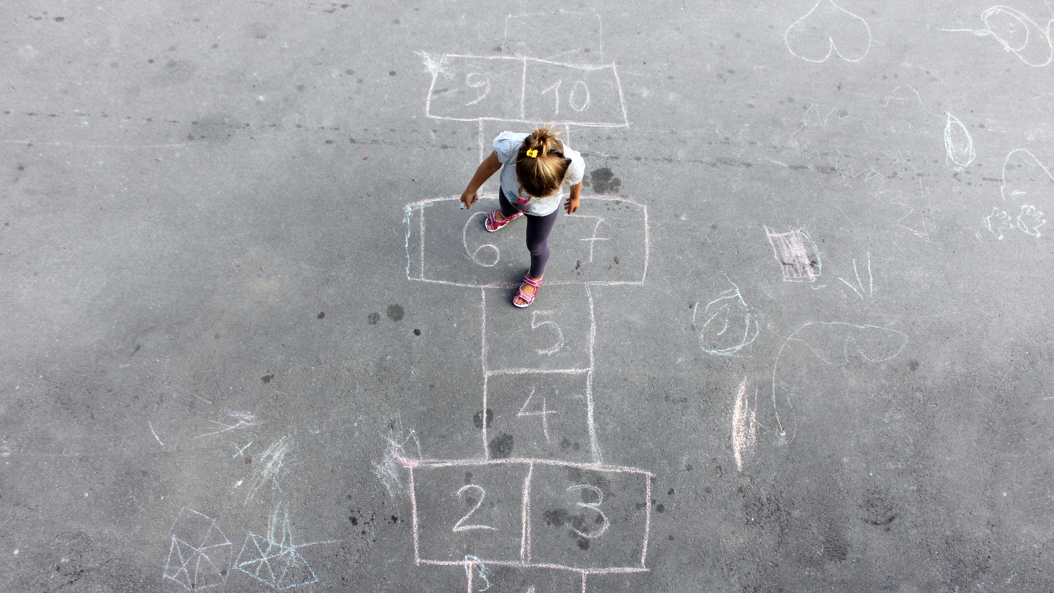 A young girl plays hopscotch