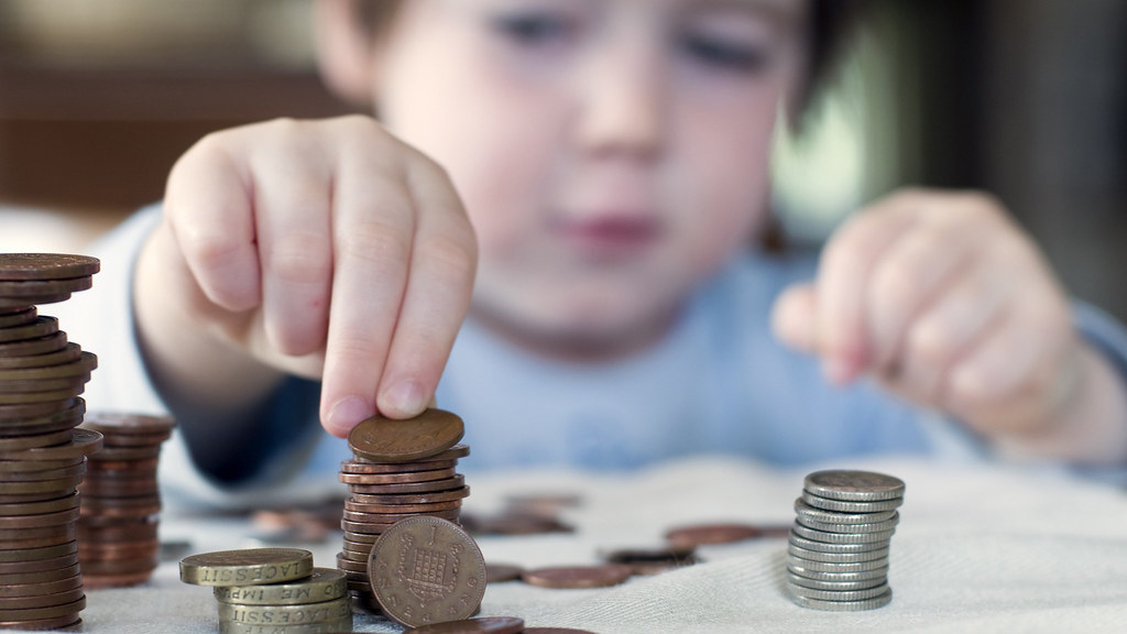 A young child counts coins