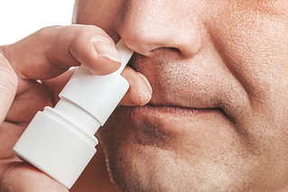 The concept of the treatment of the common cold at home. Male nose and nasal spray close up | by wuestenigel
