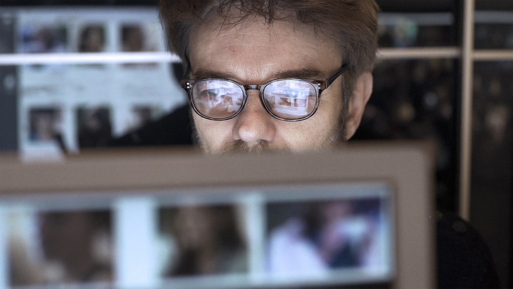 A mature man is surrounded by computer displays, he's closely watching a monitor