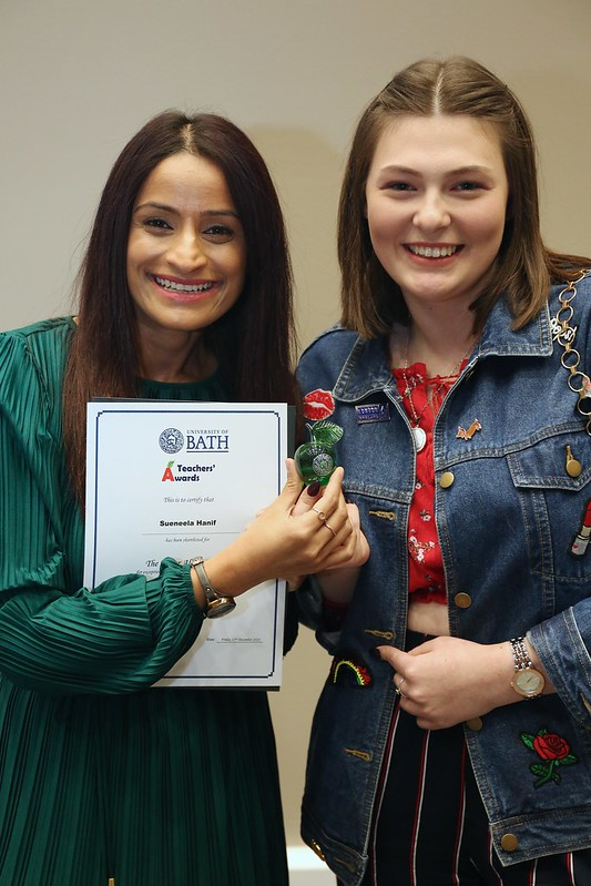 A female teacher with an award alongside a female student