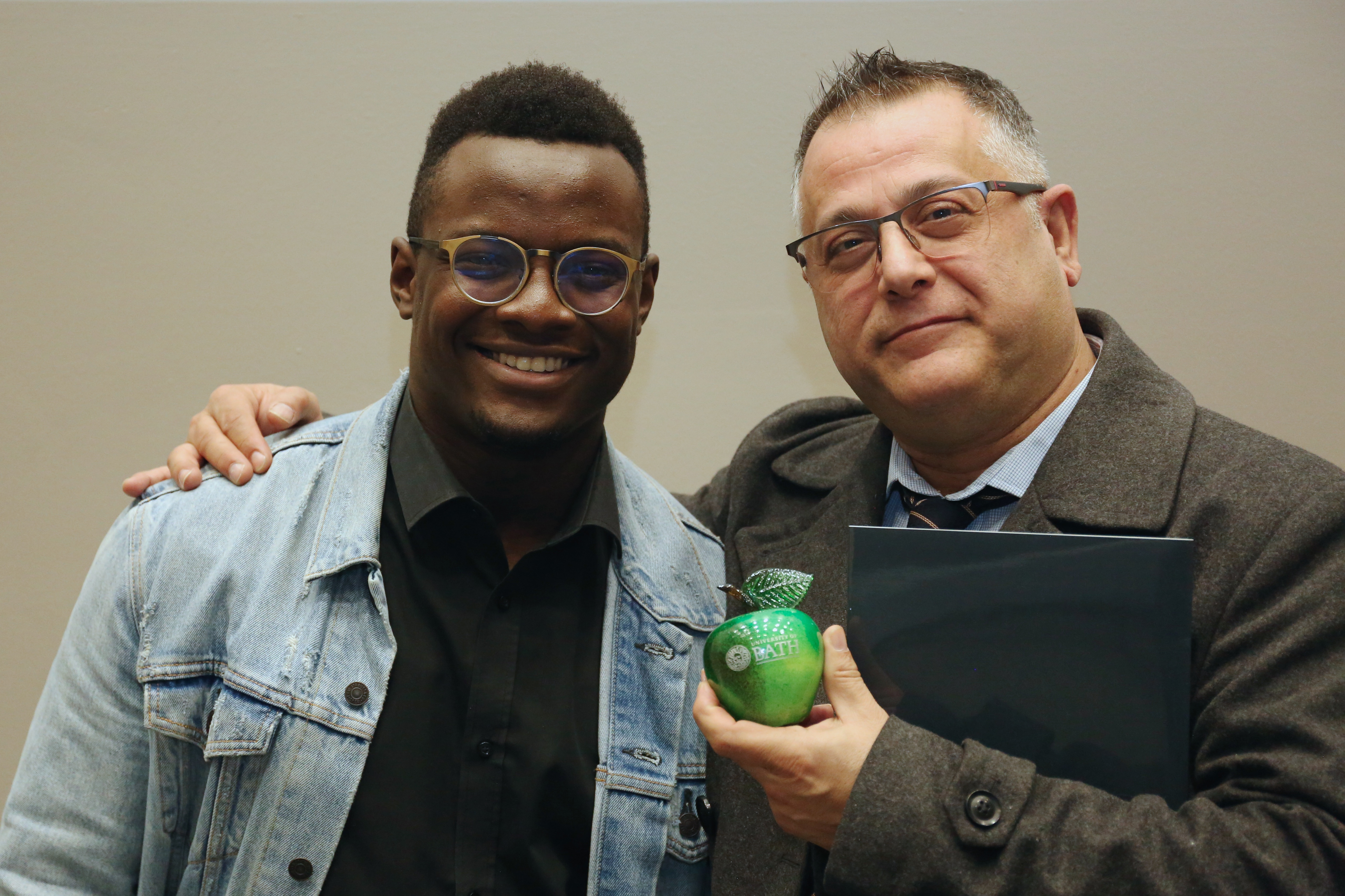 A black student with a male teacher holding his green glass apple award. Both are wearing glasses and smiling for the camera.