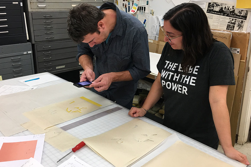 artist and graduate student review laser cut samples