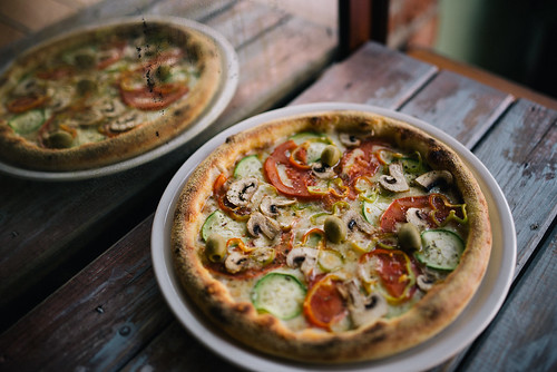 Pizza vegetariana on a wooden rustic table in the restaurant