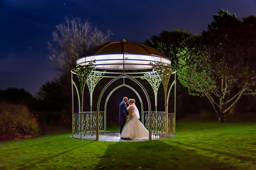 Wedding shot at the Moorland Garden Hotel on Dartmoor.  Rebecca and Carl - backlit in the dark under the Rose Arbour