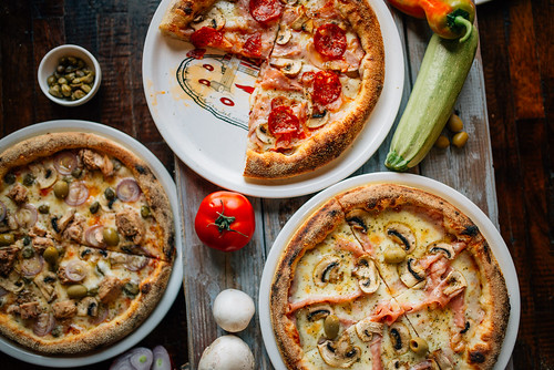 Overhead view of a variety of pizza pies. Above closeup.