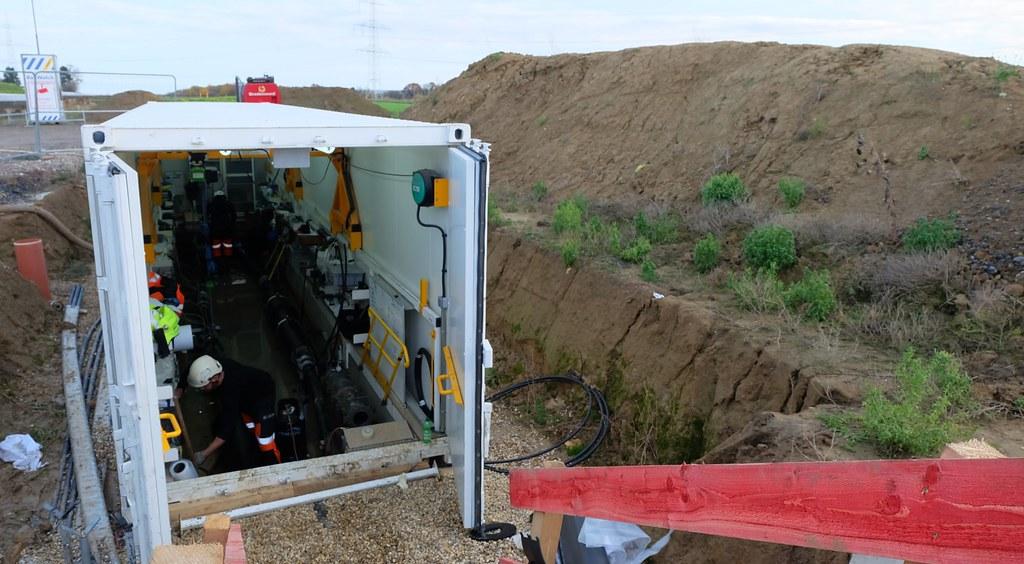 為減少對景觀以及對環境的傷害,歐洲許多電網建設走向地下化。圖為德國與比利時跨國電網建置過程,左為組合電纜線的臨時工作間,右為挖起的土丘。攝影:陳文姿