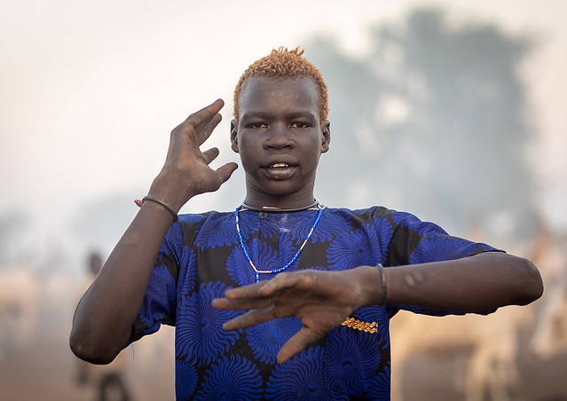 Portrait of a Mundari tribe man mimics the position of horns of his favourite cow, Central Equatoria, Terekeka, South Sudan
