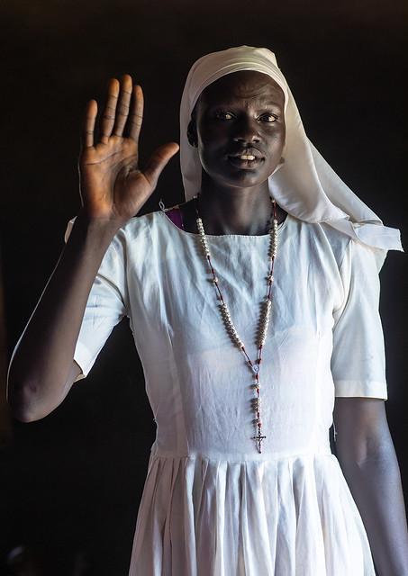 Portrait on a Mundari tribe nun with hand raised, Central Equatoria, Terekeka, South Sudan
