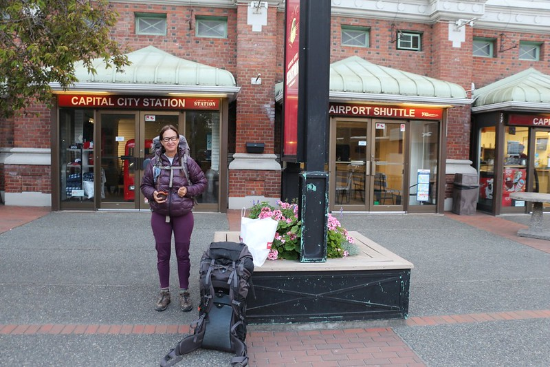 Vicki with our backpacks at the West Coast Trail Express bus stop in downtown Victoria, BC Canada