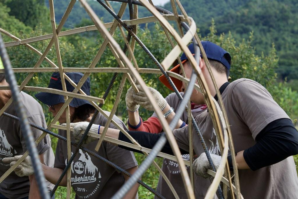 志工正努力將竹片編入鐵條。攝影:洪碩辰
