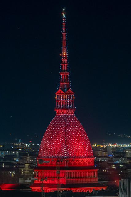 Scenic night cityscape of the Mole Antonelliana  inTurin lighted in red , Italy