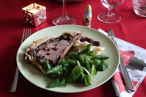 Scheibe vom Filet Wellington mit Selleriepüree, Portweinzwiebeln und mit Minzsoße angemachtem Feldsalat