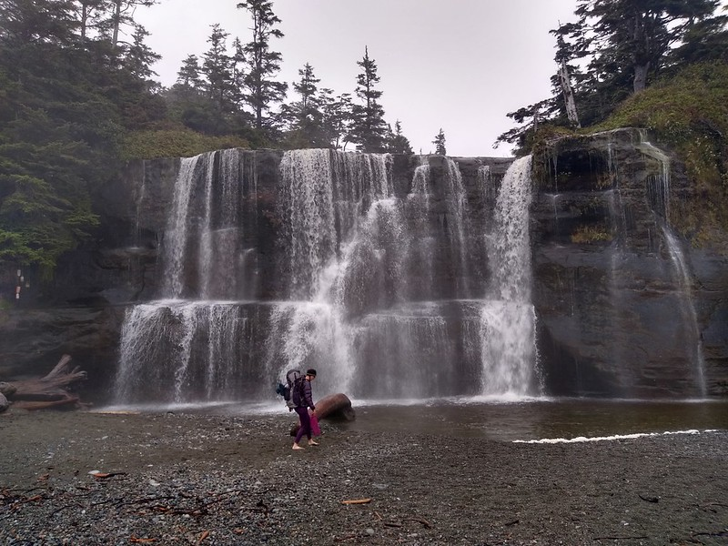 Vicki walking barefoot in front of Tsusiat Falls as we prepare to cross the river