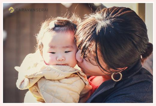 赤ちゃんにキスをするママ 冬の屋外