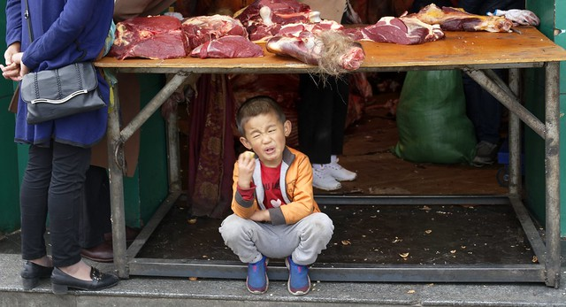 Eating a very sour apple at the butcher, Tibet 2019