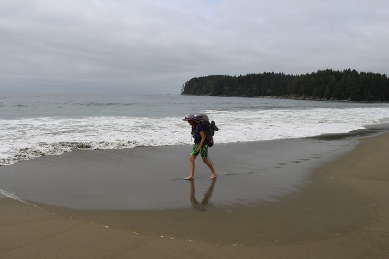 Vicki hiking barefoot on the soft sandy beach south of the Cheewhat River on the West Coast Trail