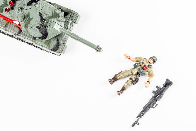 Top view, tank and toy figurine of a soldier lies on a white background. Concept of failure, death
