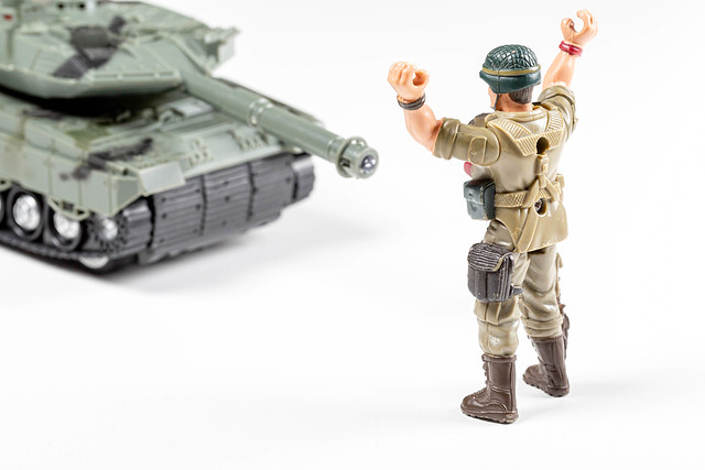 Toy soldier holds his hands up under the gun of the tank. The concept of defeat, the loser