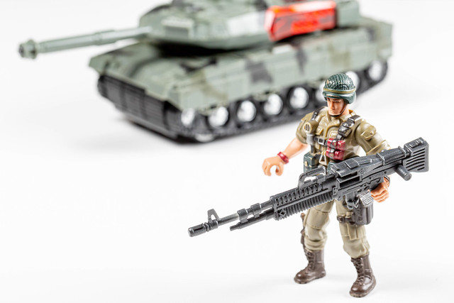 Toys soldiers with weapons in their hands and a tank behind him