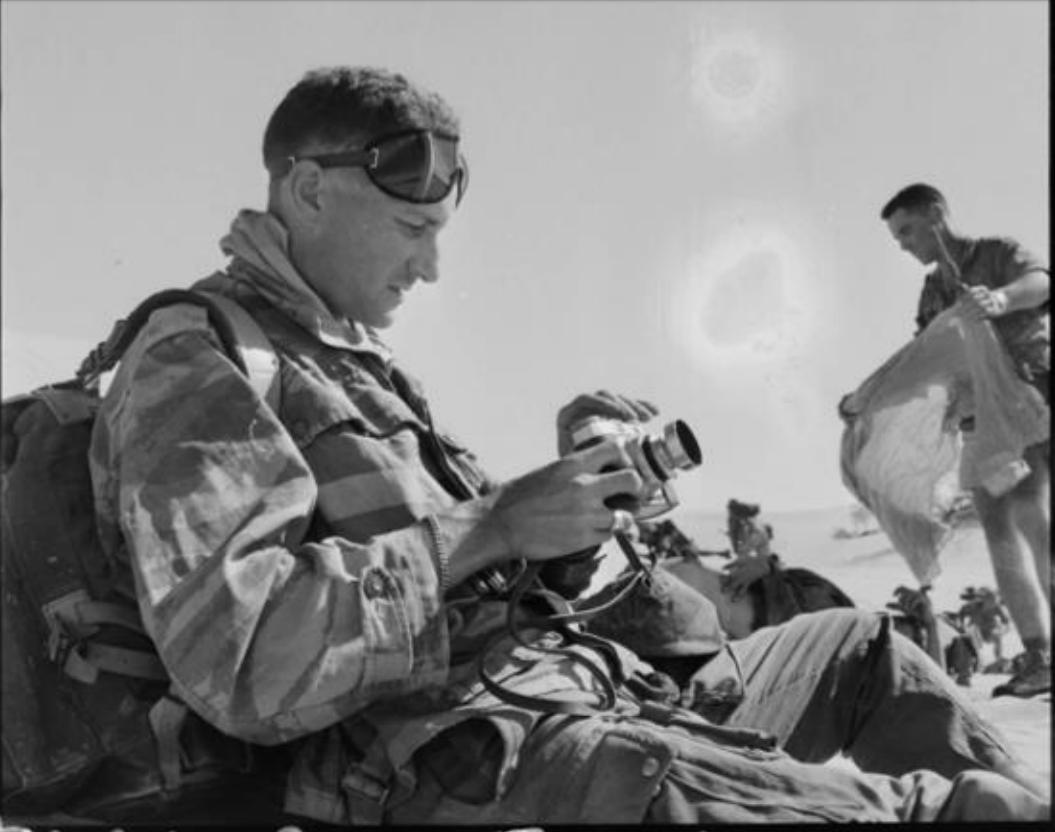 Marc Flament con su cámara el 21 de noviembre de 1957 en la batalla de Timimoun. Fotógrafo anónimo. ECPAD – Collection Flament. Référence : FLAM 57-24 R24
