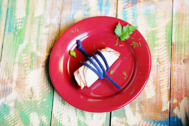 Ham in red plate, wooden background