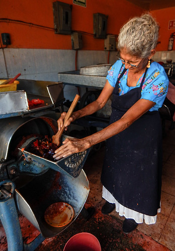 Woman grinding chiles in Puerto Escondido, Mexico