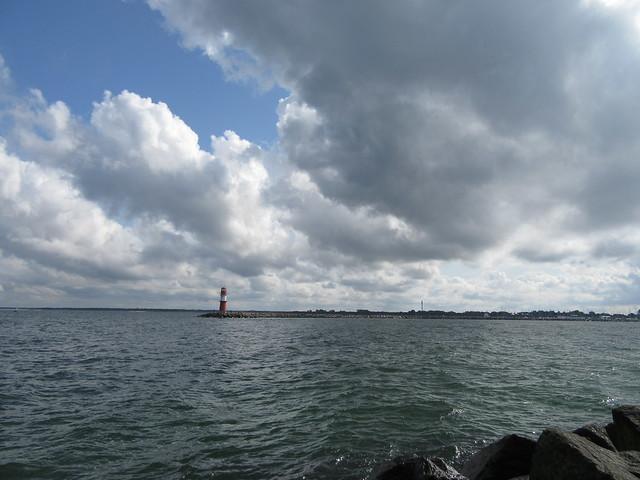 Das Bild ist in zwei Teile geteilt: Oben der Himmel mit vielen Wolken, und die blaugraue Ostsee. Die Horizontlinie wird durch die Mole gebildet, die links durch einen rot-weißen Leuchtturm begrenzt wird.