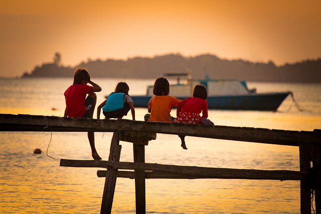 Locals Children Watch The Sun Set On Mantanani Island, Borneo