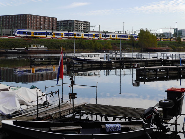 Free photo of Amsterdam city - a picture of the wide canal-water of the Dijksgracht along the train track around the city, by Fons Heijnsbroek, october 2018.