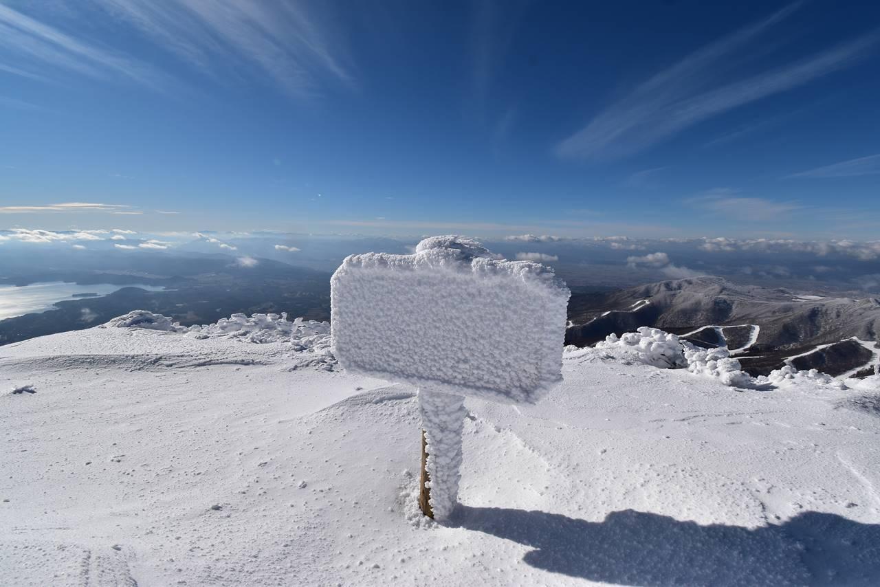 雪が凍り付いた磐梯山山頂の看板