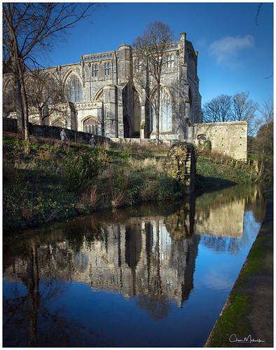 christchurch dorset uk priory church reflection water millstream trees embankment riverbank