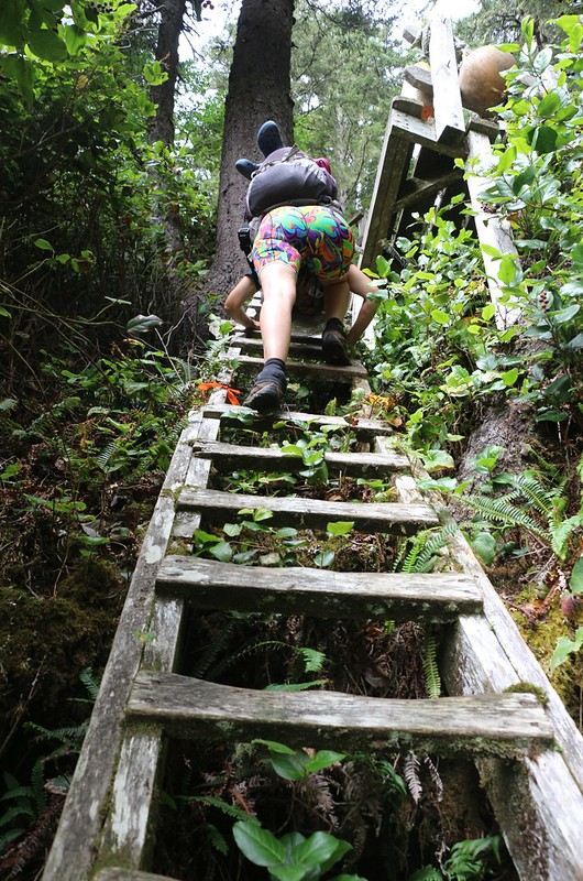 Vicki making a huge step on the ladder at Vancouver Point because of a missing step - tough with a big pack!