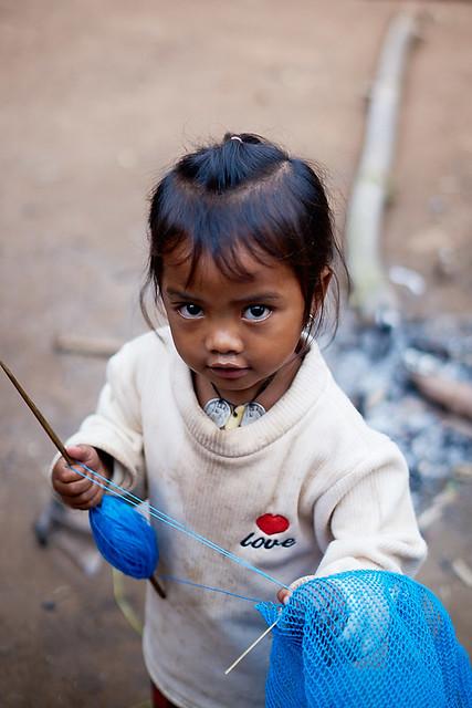 Laotian little girl sewing