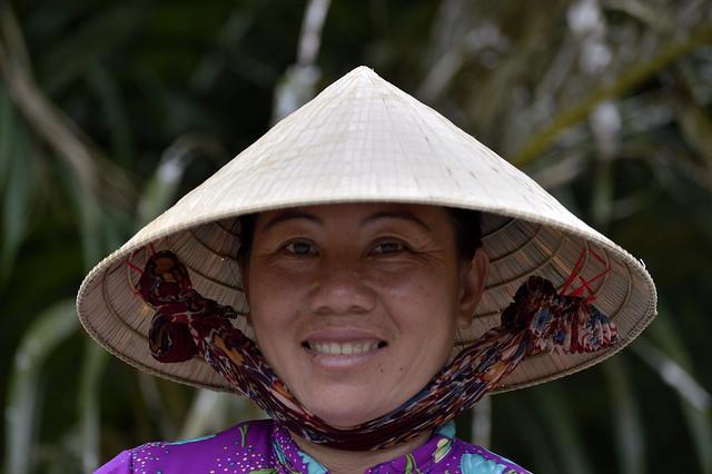 Sonrisa amable bajo el  non la. Río Mekong, Vietnam