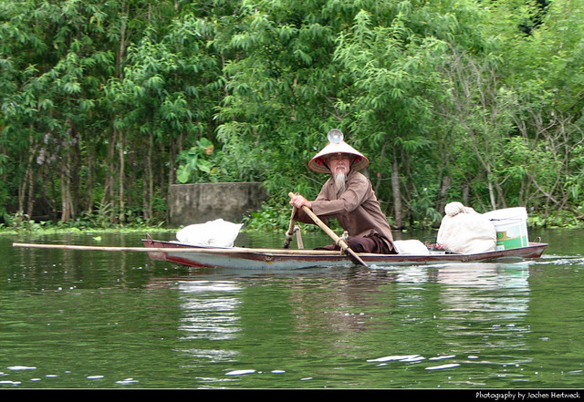 Old local man rowing a boat, Huong Tich Mountains, Vietnam