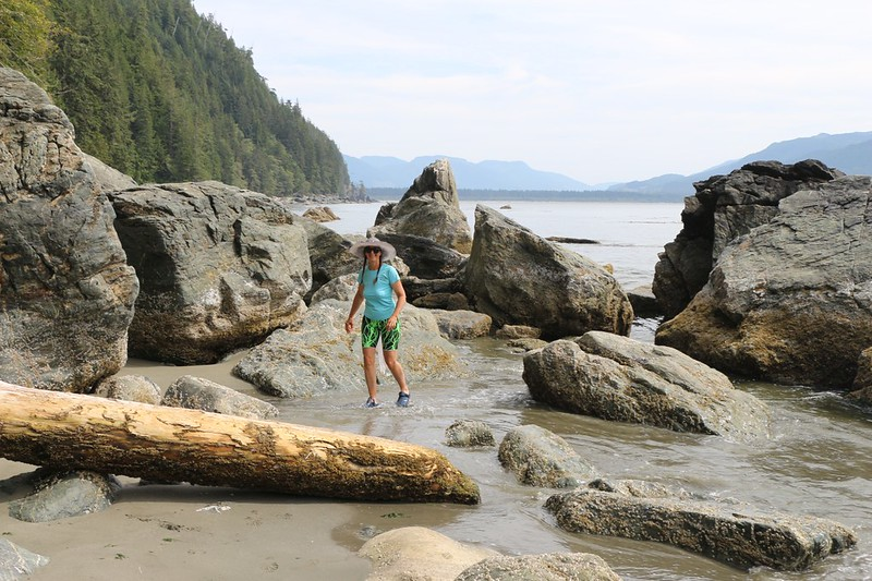 Vicki takes a walk in the water wearing only her camp shoes, at Thrasher Cove on the West Coast Trail
