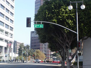 Northbound San Pedro Street approaches, proceeds and crosses at 2nd Street intersection traffic signal flashing red lights powered off followed by 1st Street intersection traffic signal red lights and pedestrian crosswalk crossing
